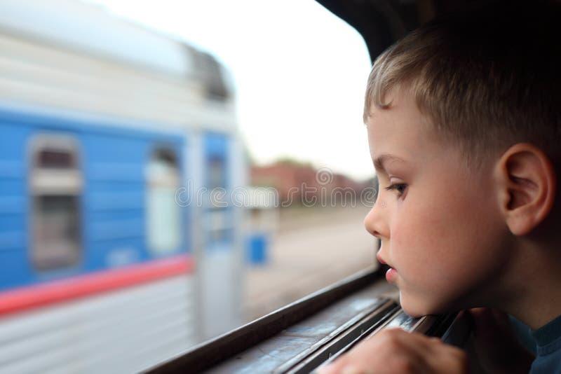 Le garçon regarde dans l'hublot du `s de train images stock