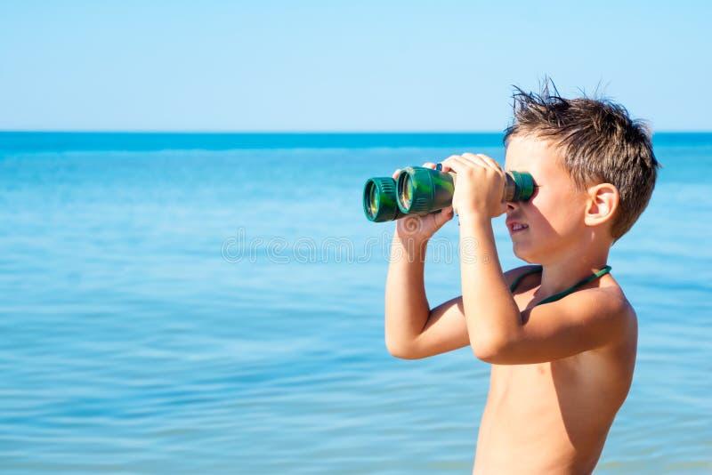 Le garçon regarde par des jumelles et voit la mer images stock