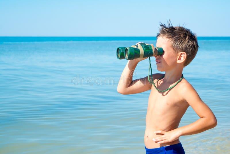 Le garçon regarde par des jumelles et voit la mer photographie stock libre de droits