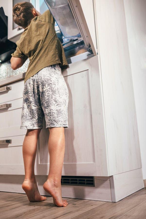 Le garçon regarde quelque chose délicieuse dans le refregerator photographie stock