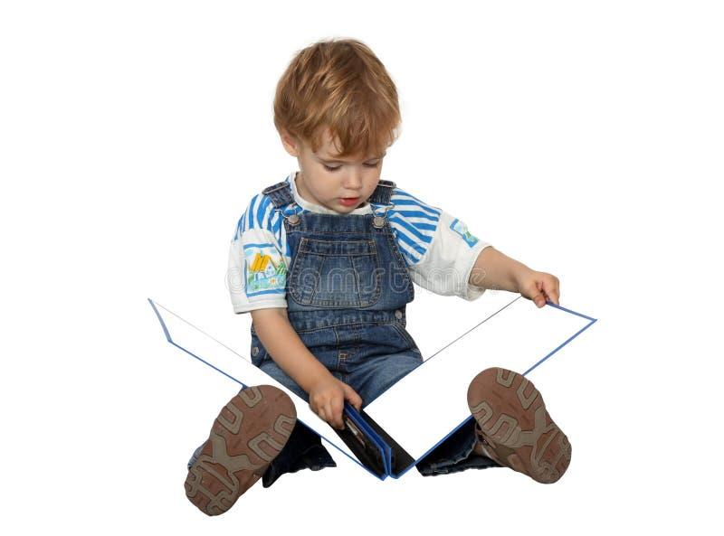Le garçon regarde sur des white pages dans l'album bleu photographie stock libre de droits