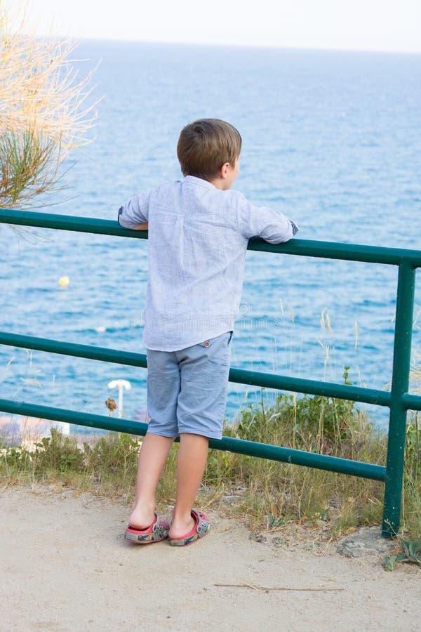 Le garçon reste la barrière proche en métal et regarde la mer photo libre de droits