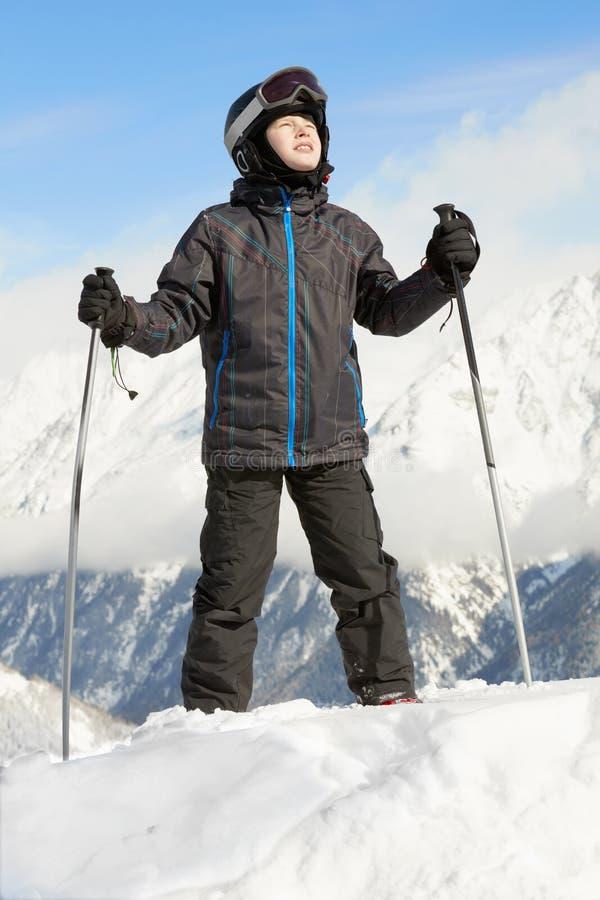 Le garçon reste se penchant sur des pôles de ski et regardant vers le haut images stock