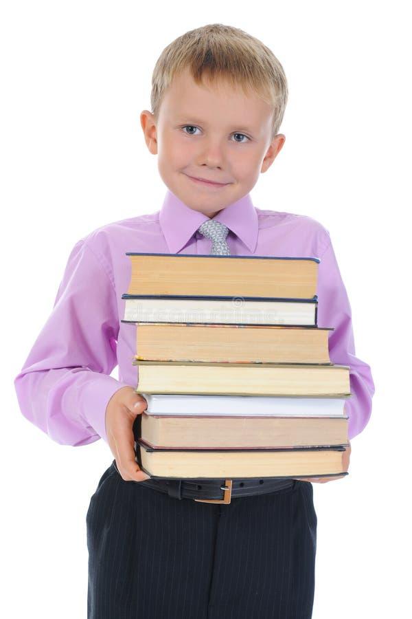 Le garçon retient une pile de livres photographie stock
