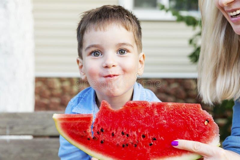 Le garçon rit et mange une pastèque avec sa mère dans le jardin photographie stock libre de droits