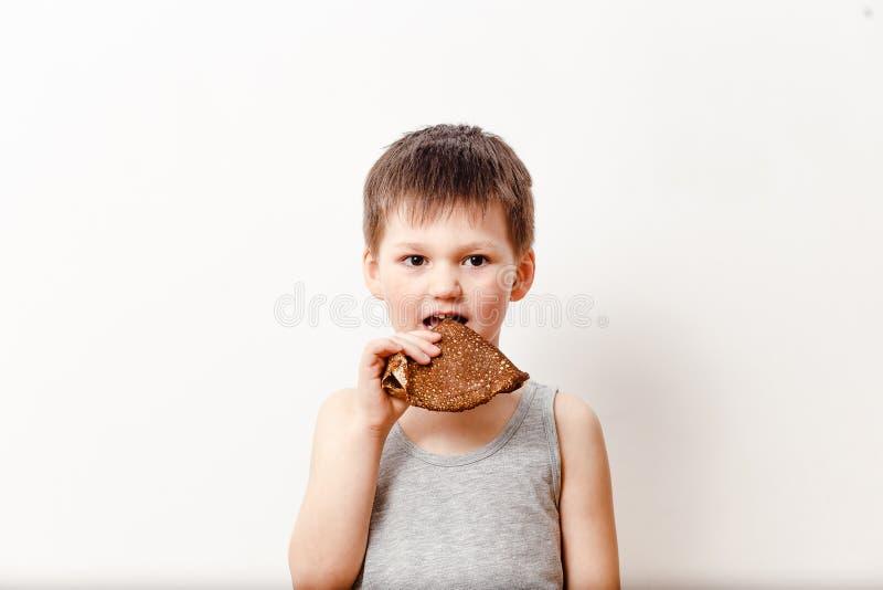 Le garçon russe de cinq ans dans un T-shirt gris mord la crêpe de beurre photographie stock