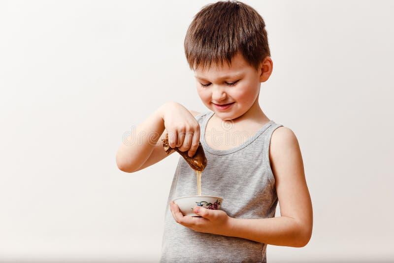 Le garçon russe de sourire de cinq ans enduit une crêpe roulée de beurre dans le miel liquide sur un fond blanc Maslenitsa russe photos libres de droits