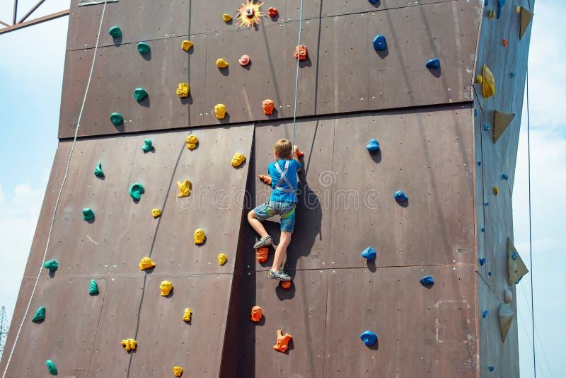 Le garçon s'élève jusqu'au dessus d'un mur artificiel en parc extrême, se tenant sur une corde de sécurité images stock