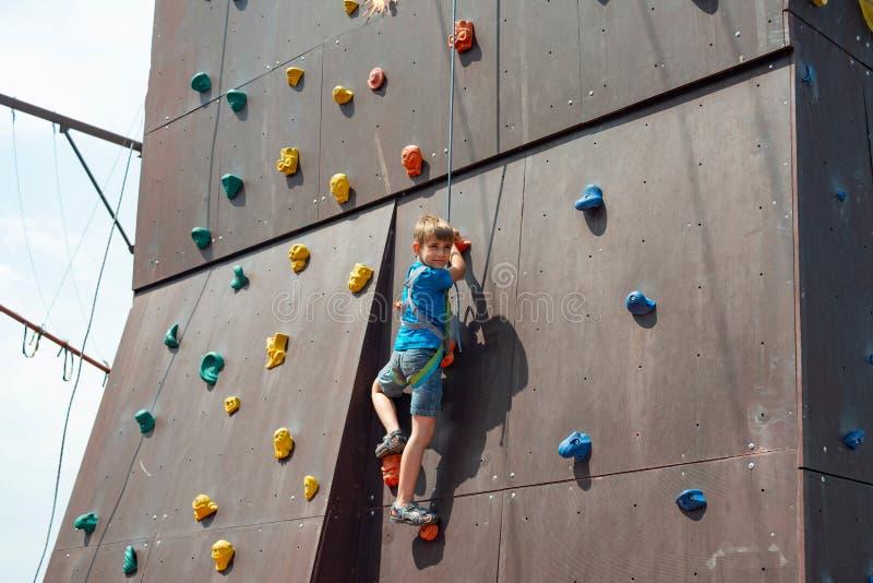 Le garçon s'élève jusqu'au dessus d'un mur artificiel en parc extrême, se tenant sur une corde de sécurité photographie stock