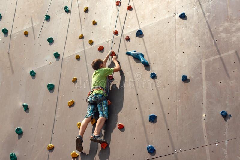 Le garçon s'élève jusqu'au dessus d'un mur artificiel en parc extrême, se tenant sur une corde de sécurité photographie stock libre de droits