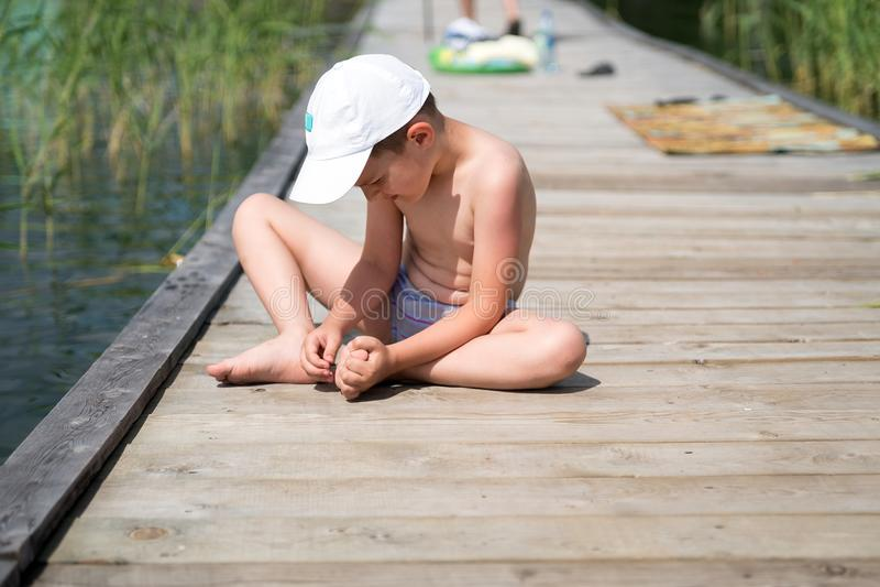 Le garçon, s'asseyant sur un plancher en bois, avec sa main retire un éclat dans son pied image libre de droits