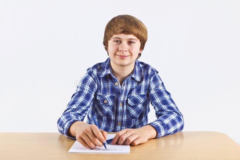 Le garçon s'assied à son bureau et fait son travail photo libre de droits