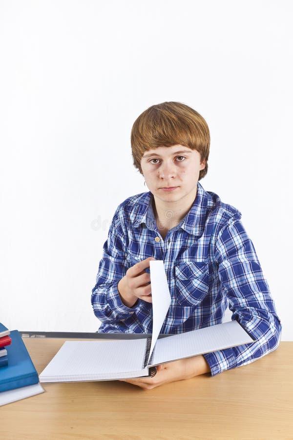 Le garçon s'assied à son bureau et fait son travail photos stock