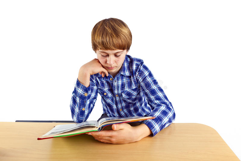 Le garçon s'assied à son bureau et fait son travail images stock