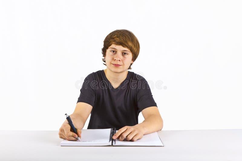 Le garçon s'assied à son bureau et fait son travail photographie stock libre de droits