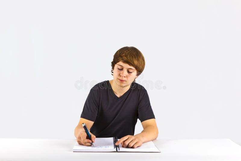 Le garçon s'assied à son bureau et fait son travail photographie stock