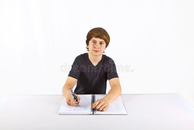 Le garçon s'assied à son bureau et fait son travail image libre de droits