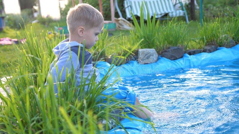 Le garçon s'assied à un petit lac L'enfant crée éclabousse de l'eau de ses pieds Jour d'été chaud Enfance heureux photographie stock libre de droits
