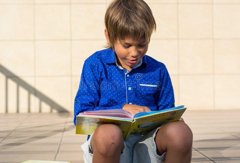 Le garçon s'assied sur les étapes devant l'école et lit le livre photos libres de droits