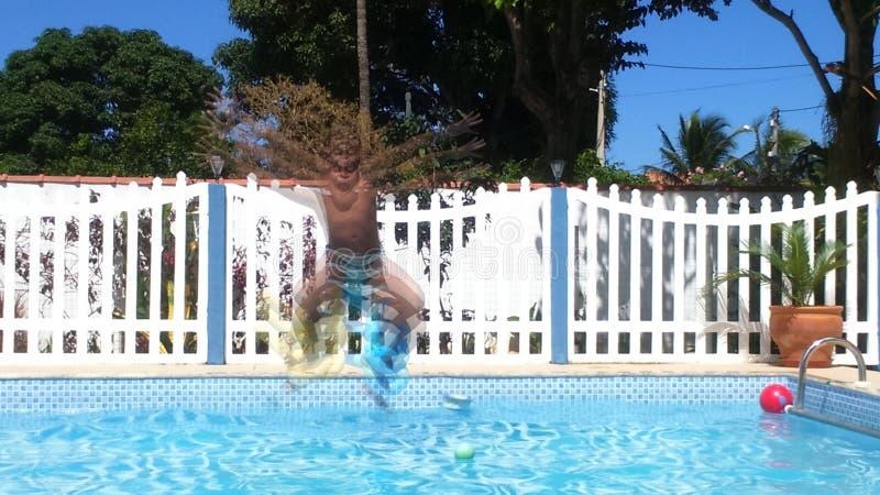 Le garçon sautant dans l'eau image libre de droits