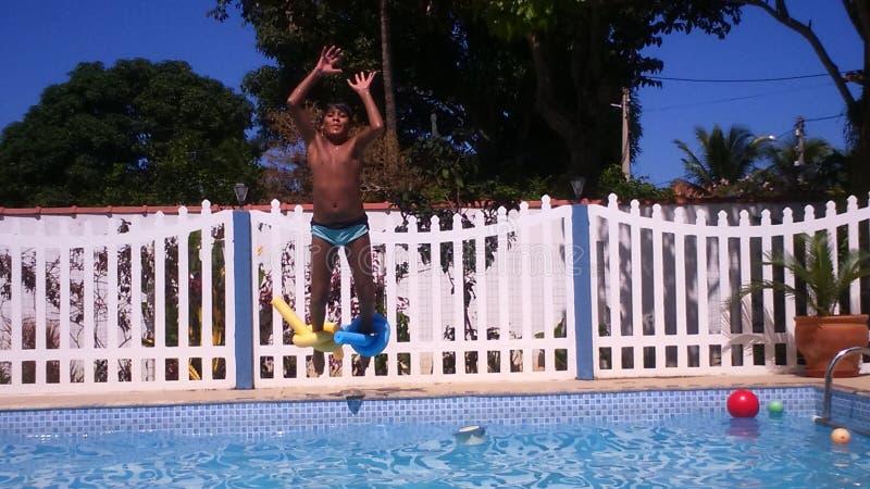 Le garçon sautant dans l'eau photos libres de droits