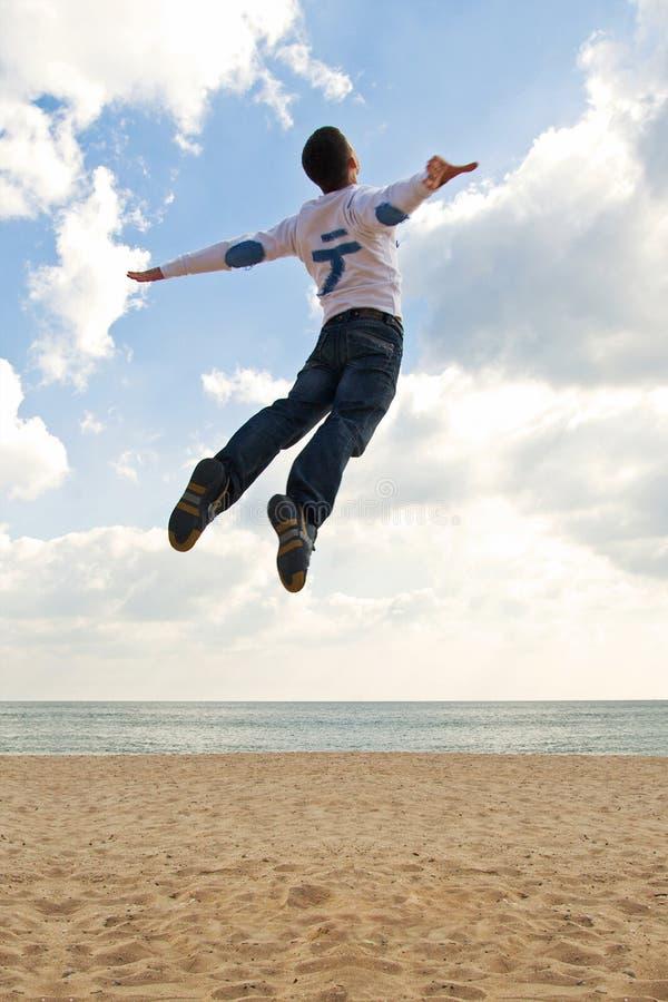 Le garçon sautant dans le ciel photo stock