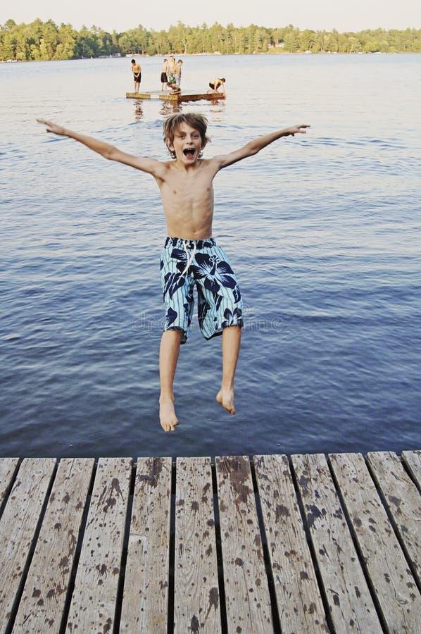 Le garçon sautant dans le lac photo stock