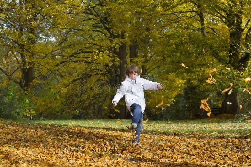 Le garçon sautant et jouant avec les feuilles d'automne d'or photographie stock libre de droits