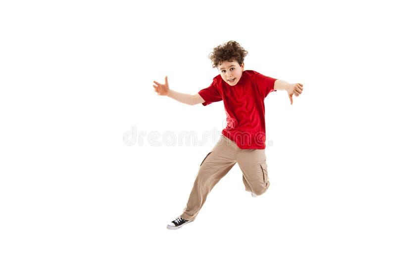 Le garçon sautant, fonctionnement d'isolement sur le fond blanc photo libre de droits