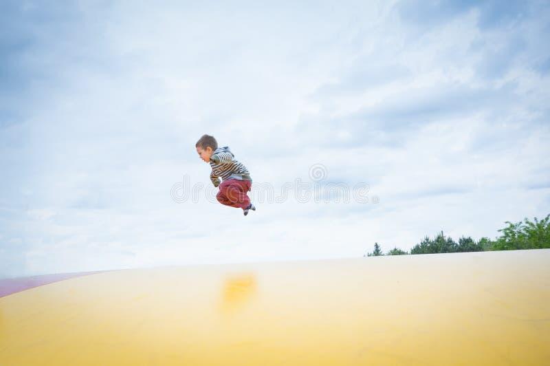 Le garçon sautant haut sur un trempoline extérieur photo libre de droits