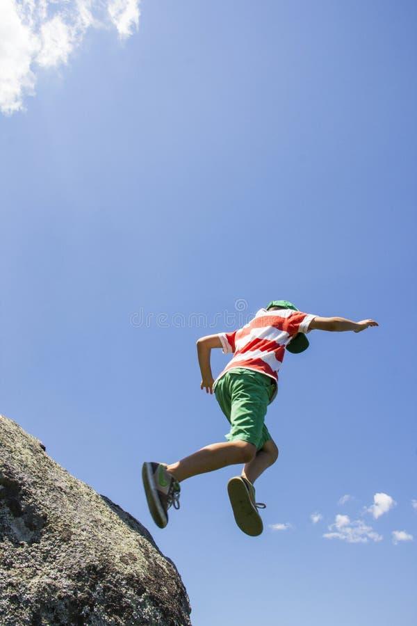 Le garçon sautant outre d'une roche photos libres de droits