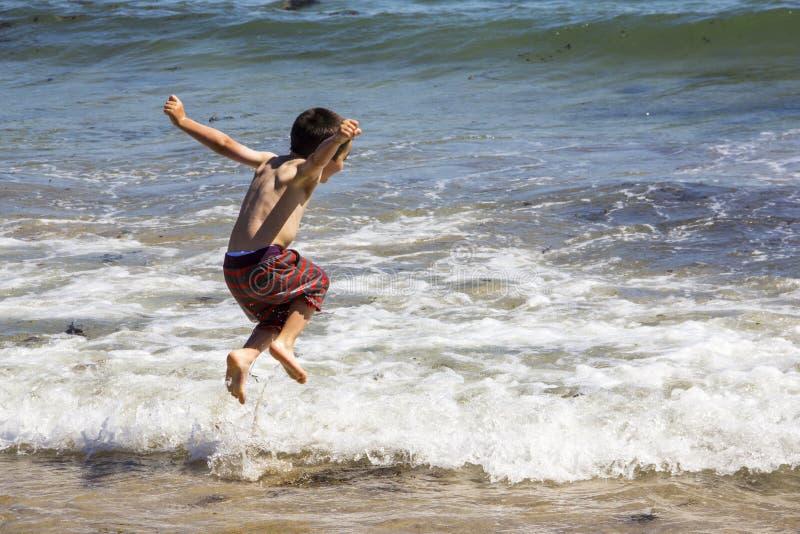 Le garçon sautant par-dessus les vagues à l'océan image stock