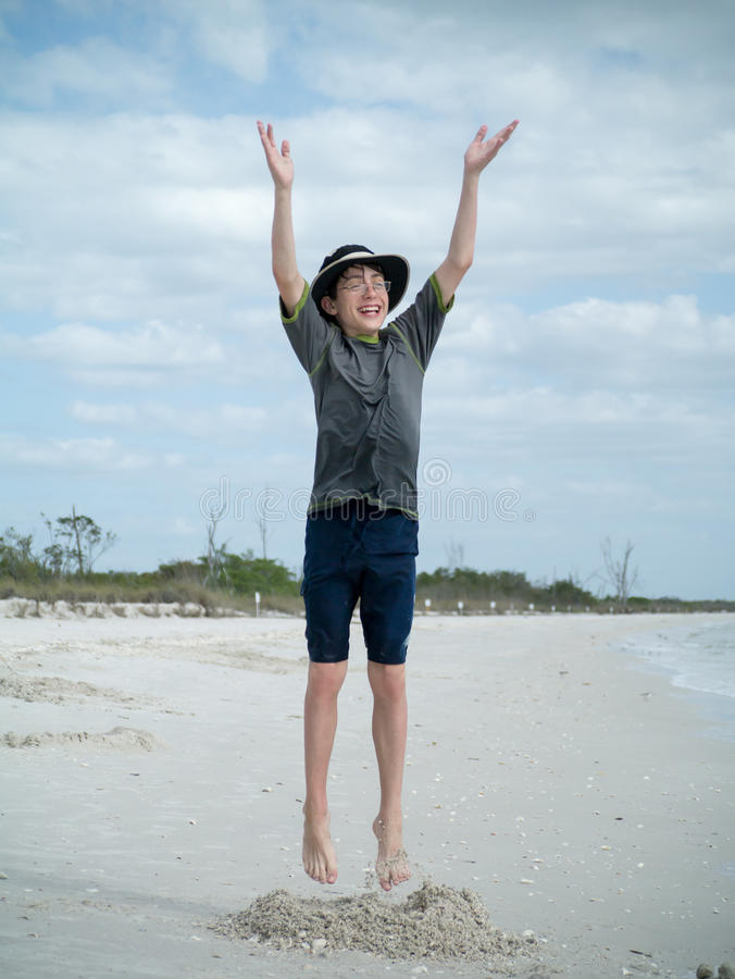 Le garçon sautant pour la joie sur la plage images libres de droits