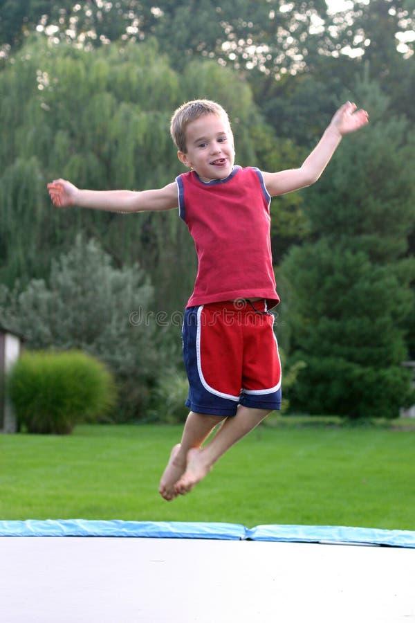 Le garçon sautant sur le tremplin images stock