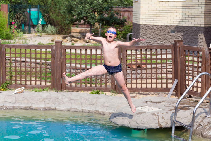 Le garçon saute dans la piscine photographie stock