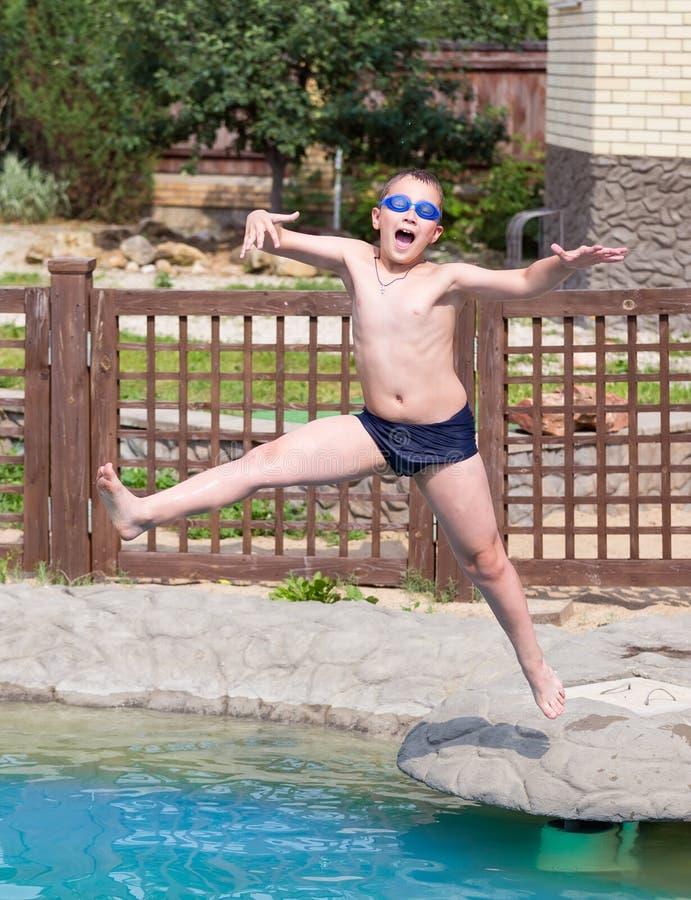 Le garçon saute dans la piscine photo libre de droits