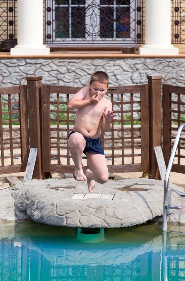 Le garçon saute dans la piscine image stock