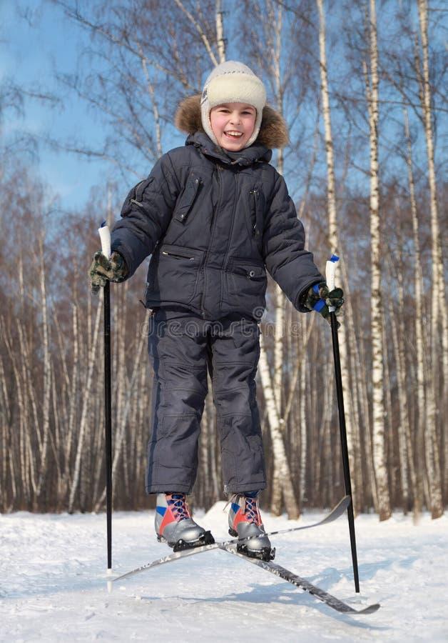 Le garçon saute et croise les skis transnationaux photo stock