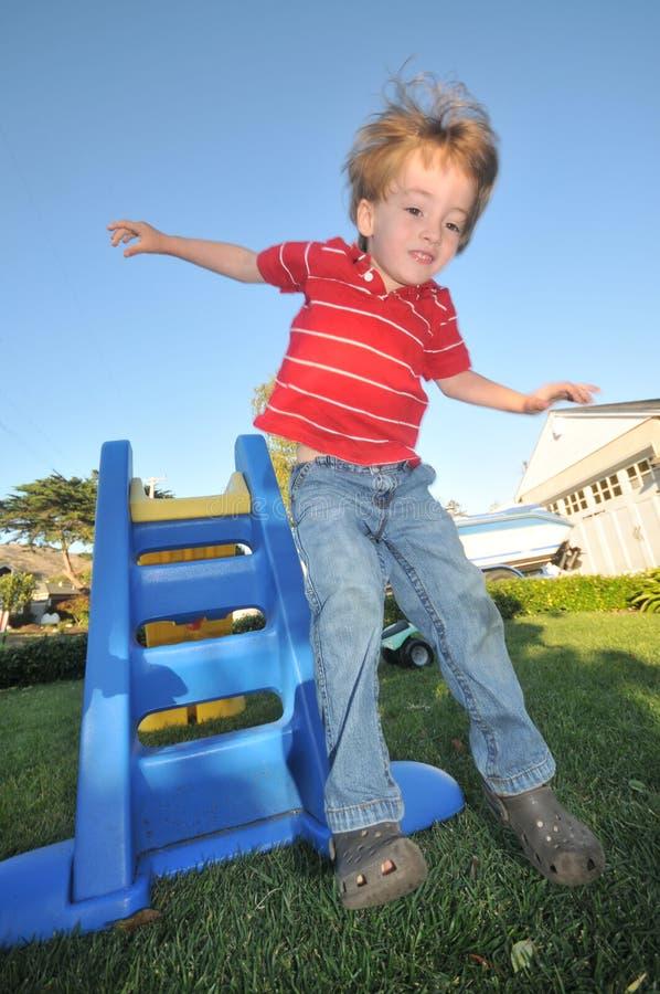 Le garçon saute outre d'une glissière sur l'herbe images stock