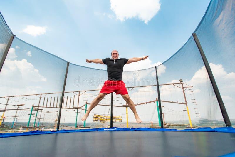 Le garçon saute sur un trempoline en parc d'attractions, exécutant de divers cascades images stock