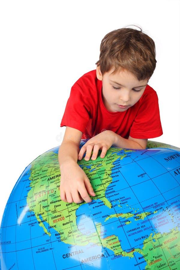 Le garçon se penche sur le globe gonflable d'isolement sur le blanc images stock