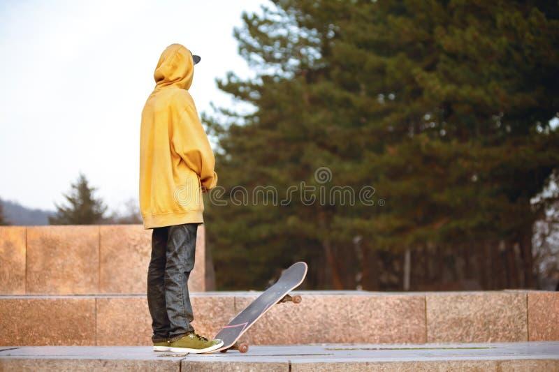 Le garçon se tient avec une planche à roulettes dans les lumières de coucher du soleil photos libres de droits
