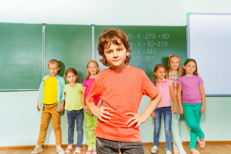Le garçon se tient devant des enfants près du tableau noir images libres de droits
