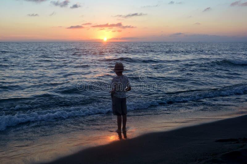 Le garçon se tient sur la plage au crépuscule images libres de droits