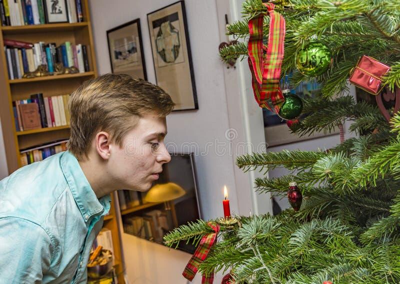 Le garçon souffle la bougie rouge à l'arbre de Noël photographie stock