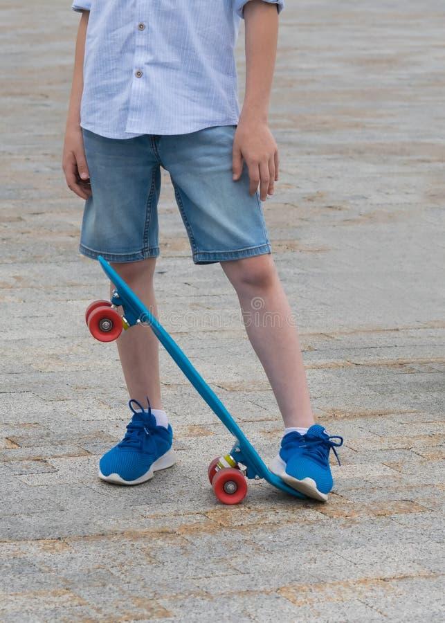 Le garçon soulève le bord des sports embarquent avec son pied, pour porter dans des ses mains photos libres de droits