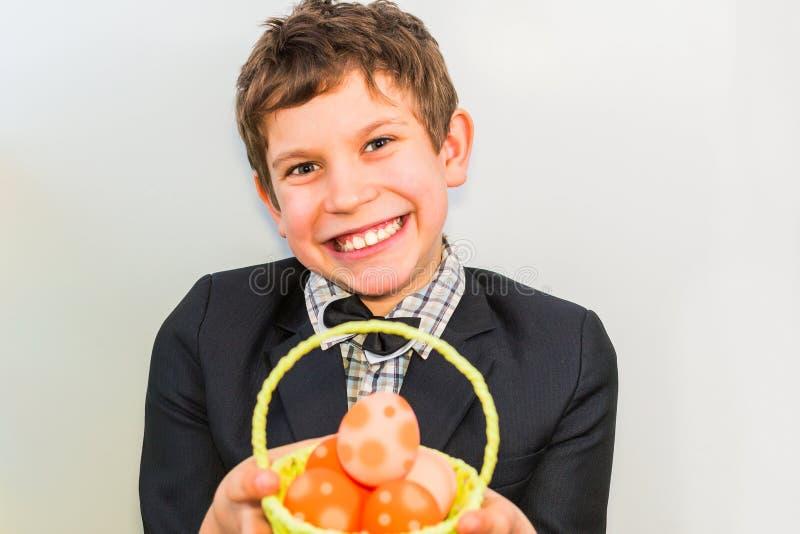 Le garçon sourit et tient un panier des oeufs Le concept de Joyeuses Pâques photographie stock