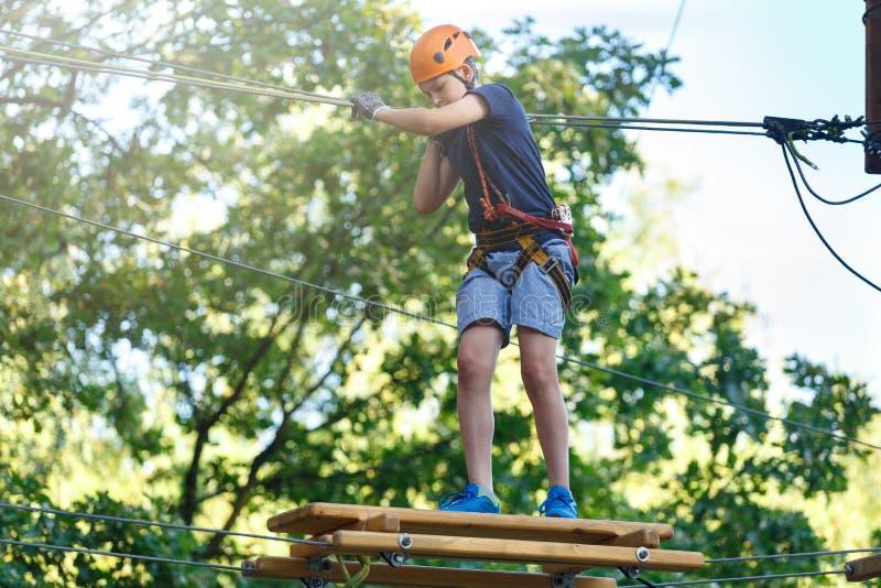 Le garçon sportif, jeune, mignon dans le T-shirt blanc passe son temps dans le parc de corde d'aventure dans le casque et l'équip image stock