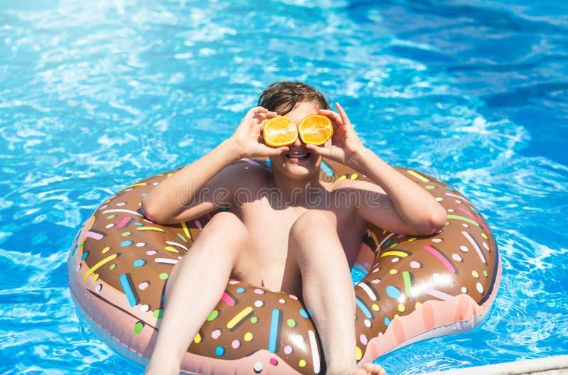 Le garçon sportif mignon nage dans la piscine avec l'anneau de beignet et a l'amusement, sourires, oranges de prises vacances ave photographie stock