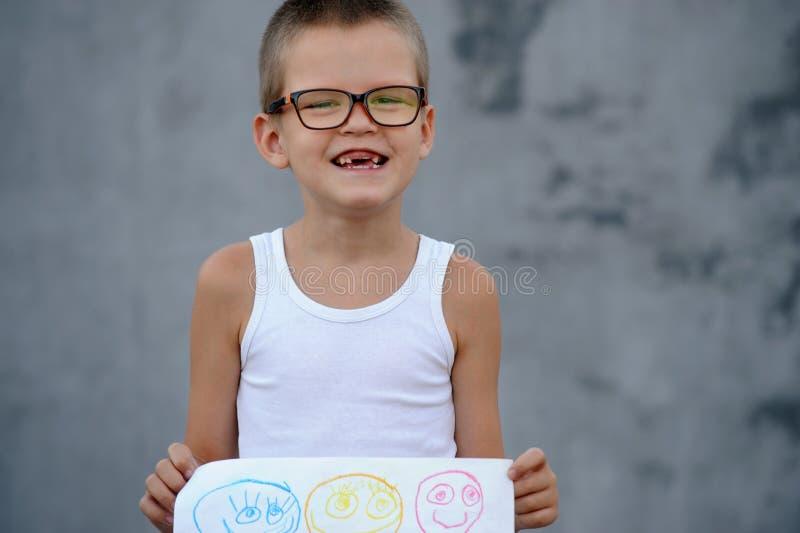 Le garçon supérieur dans une famille nombreuse va à l'école et montre ses dessins images libres de droits